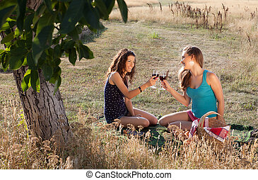Happy picnic - Happy young women tasting wine during a...