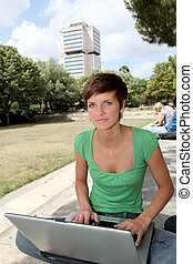 Student with laptop computer in college park
