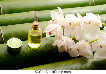 Essential oil and white orchid flowers on a tightly arranged...