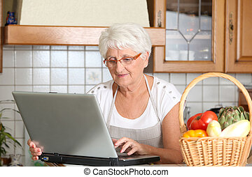Elderly woman in kitchen with laptop computer