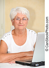 Closeup of elderly woman with laptop computer