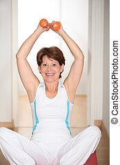 Closeup of senior woman lifting weights
