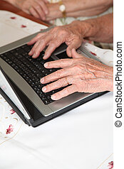 Closeup on elderly person hands on computer desk