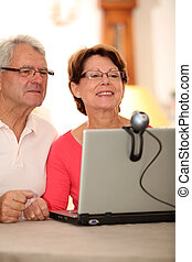 Closeup of senior couple sending messages through webcam