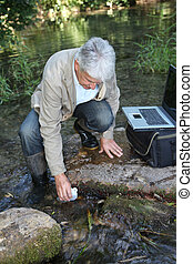 Biologist testing quality of stream water