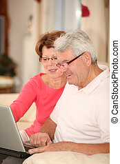 Senior couple sitting in sofa with laptop computer
