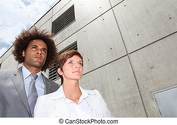 Closeup of businesspeople in front of concrete wall