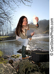 Woman testing quality of natural water