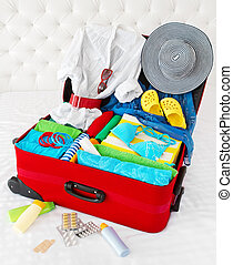 Travel suitcase packed for vacation with personal belongings