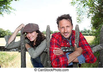 Couple leaning on fence in country field
