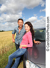 Couple standing by convertible car