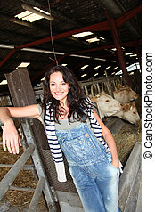 Smiling woman farmer standing in barn
