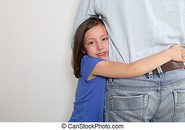 Little girl putting arms around her fathers waist