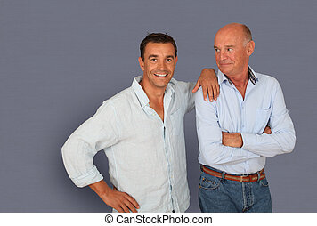 Portrait of father and son on grey background