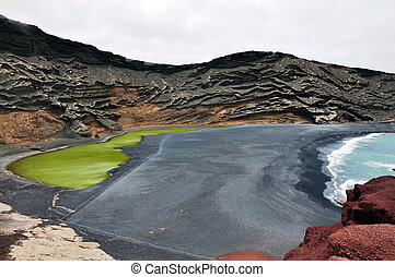 The green lake in Lanzarote - Volcano crater as black sand...