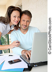 Couple working at home on laptop computer