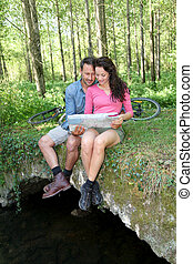 Couple sitting on a bridge in forest