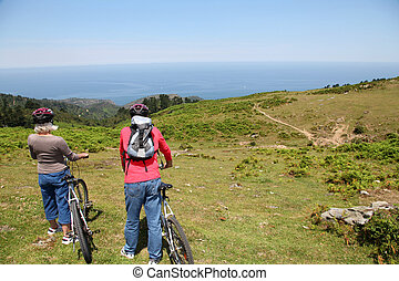 Senior couple looking at scenery during bike ride