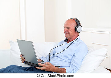 Senior man listening to music with headphones