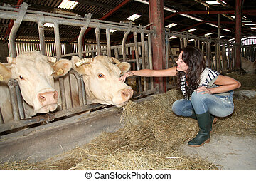 Smiling woman farmer petting cows