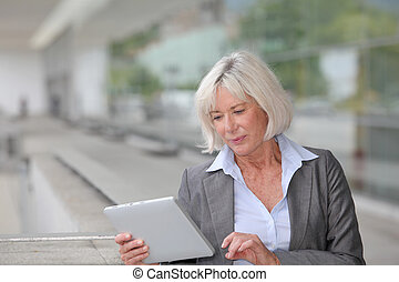 Businesswoman using electronic tablet outside airport