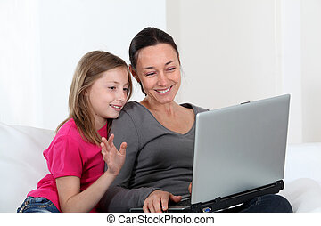 Mother and daughter using laptop computer at home