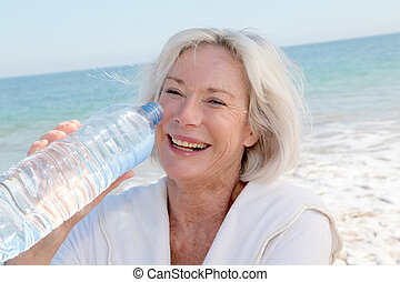 Senior woman drinking water from bottle