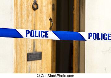 Police tape across an open door - Police tape strung across...