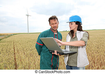 Farmer and engineer in wheat field with wind turbines in...