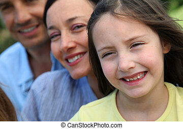 Portrait of smiling little girl with parents in background