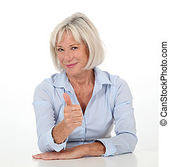 Portrait of senior woman showing thumb up