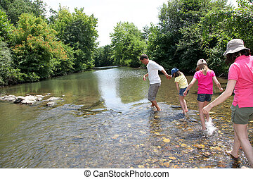 Family crossing river in summer