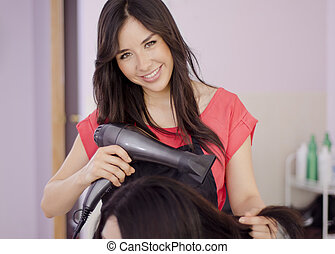 Hairstylist with a blow dryer - Pretty female hairstylist...