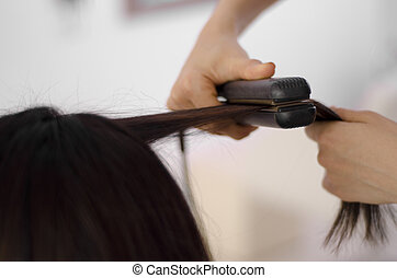 Woman getting her hair straightened - Closeup of a woman...