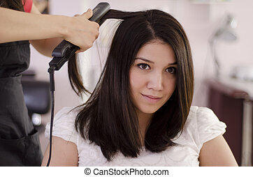 Woman getting her hair straightened - Female hairstylist...
