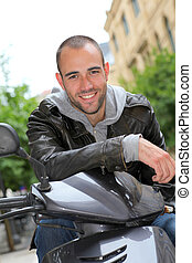 Portrait of young man sitting on motorcycle in town