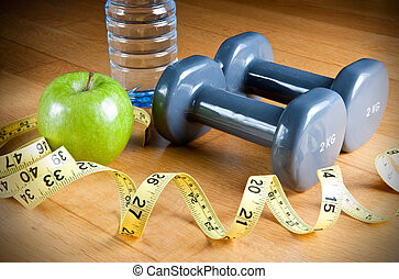 Exercise and Healthy Diet - Pair of dumbbells, green apple,...