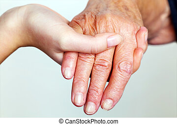 old and young hand with walking stick - a lte and young hand...