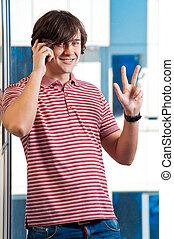 Smiling young man speaking on cellphone - indoor