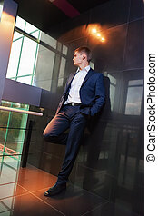 Young businessman resting on wall looking towards
