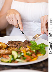 Woman eating in restaurant - This is closeup of woman eating...