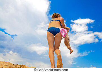 This is a photograph of mother playing with baby on beach
