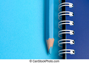 Blue pencil and spiral of notebook - macro