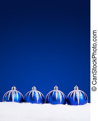 Glittering blue christmas balls on dark background. Copy...