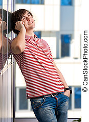 Smiling young man speaking on cellphone