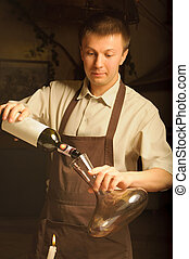 A sommelier pouring red wine into decantor