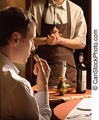 A young man sniffing the cork of a wine bottle