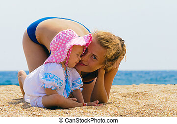 Baby with her mother on the beach