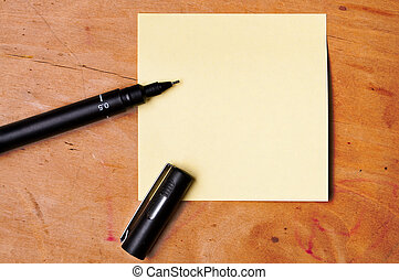 sticky note with black pen on wooden board