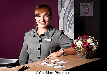 Young smiling woman at the reception desk